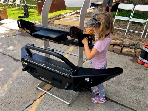 Sydney cleaning the dust of the FJ Cruiser Phantom bumper display.